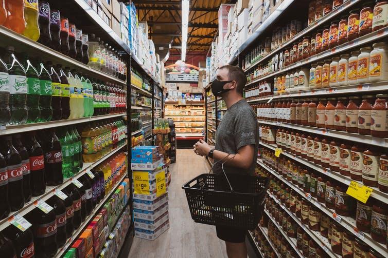 Un homme masqué pusse un chariot dans une épicerie